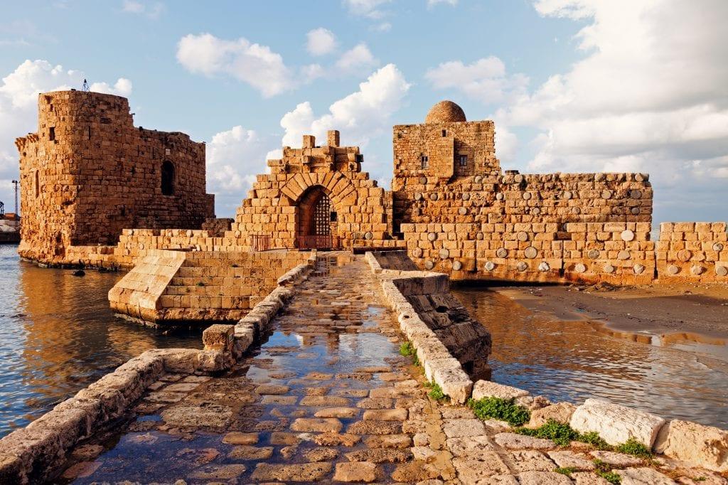 Castillo del mar de Sidón: ves un pequeño edificio de piedra que parece un fuerte, colocado en el mar.  Conduciendo al castillo hay un camino de piedra sobre el agua.