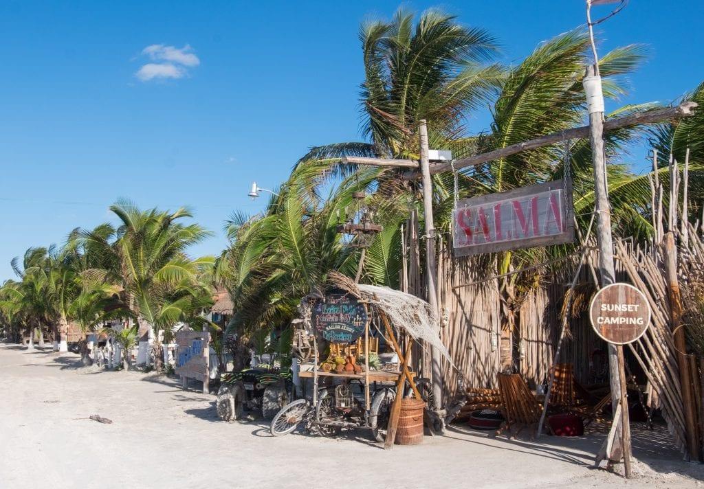 Beach shacks and bars beneath palm trees on the beach in Holbox, Mexico.