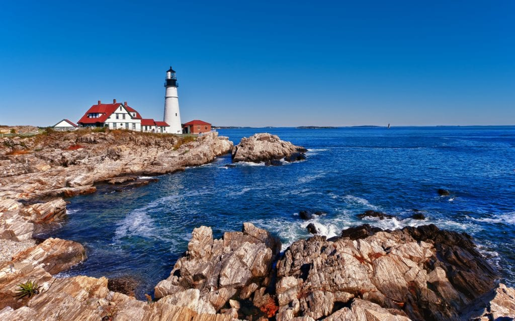 The bright white Portland Head Lighthouse, standing on a rocky outcropping jutting into the bright blue ocean.