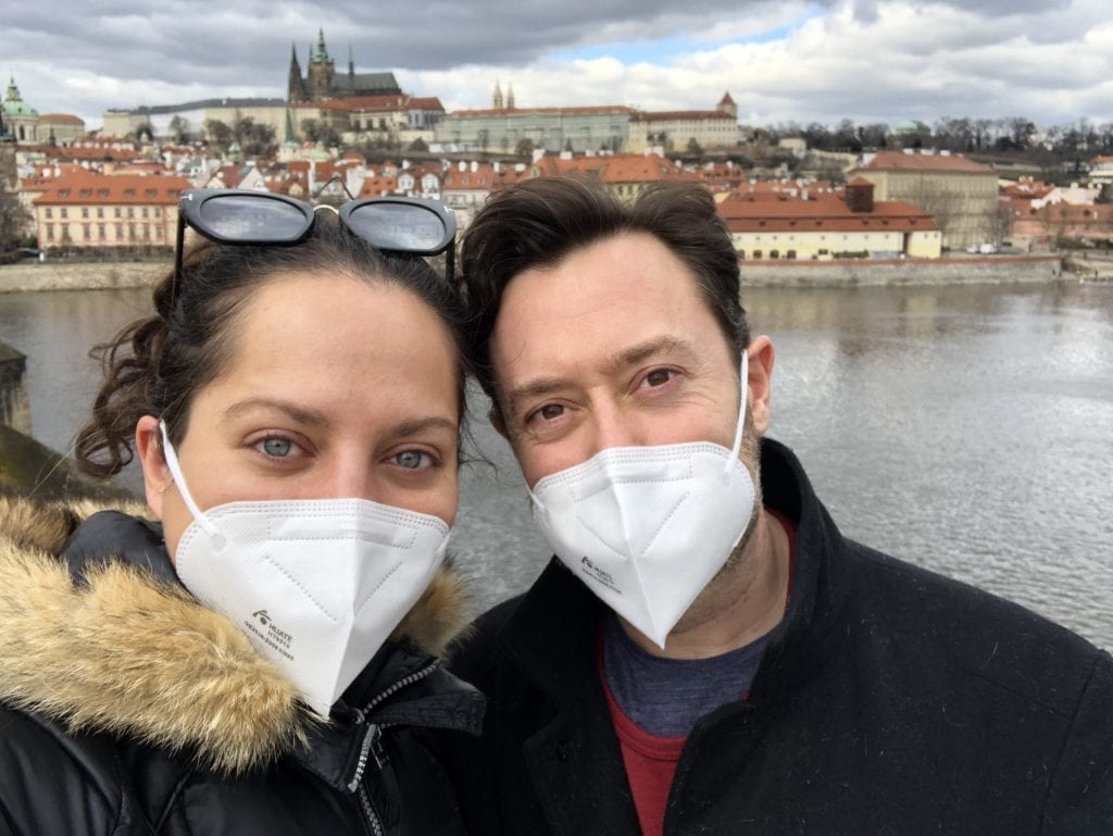Kate and Charlie take a selfie together outside on the Charles Bridge in Prague. You can see Prague Castle rising behind them above the river. They both wear white pointy respirator face masks and smile for the camera.