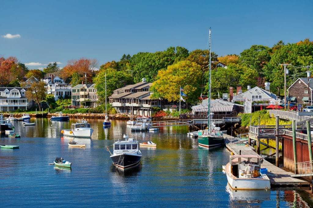 Fishing boats docked in a smooth harbor in front of waterfront homes in Ogunquit, Maine. In the background are trees just starting to turn red and yellow.