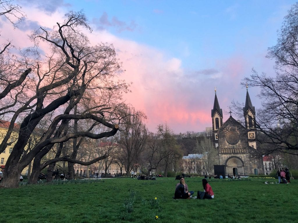 Karlinske Namesti -- my square! A green open space, like a park, in front of a church with two steeples. People are sitting in groups on the grass. The trees are still bare and the sky is a pink, blue and purple sunset.