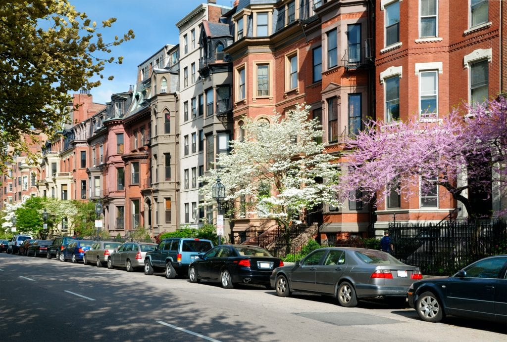 Brownstones with bay windows in Back Bay, cars parked along the sidewalk. There are several trees flowering white and pink.