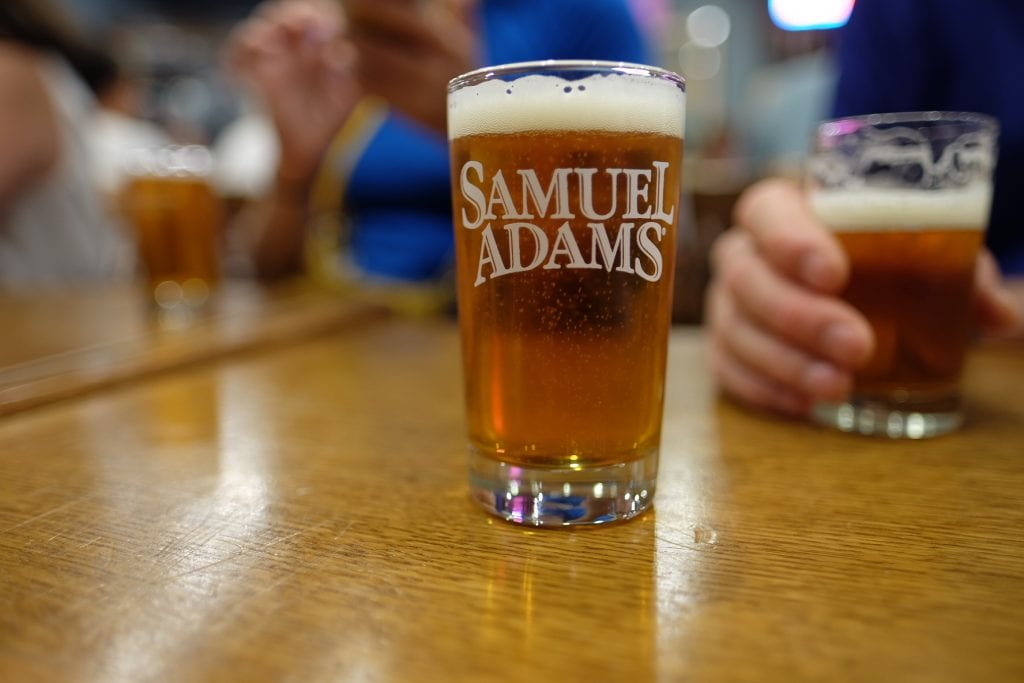 """A small beer in a glass emblazoned with """"Samuel Adams."""""""