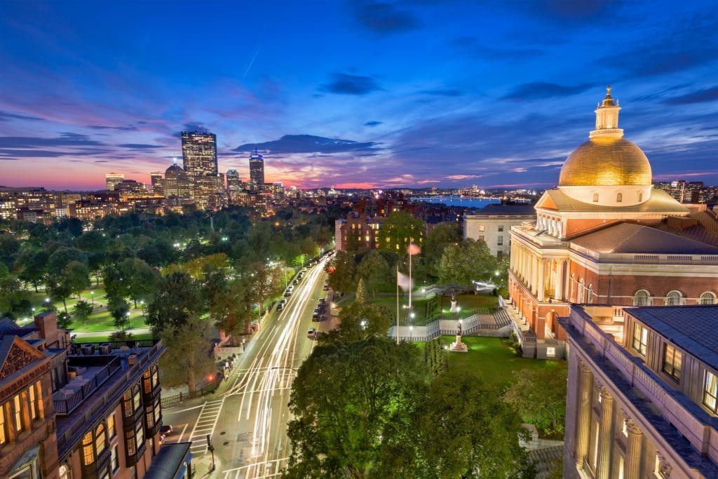 A view of Boston at night: the golden-domed state house on the right, the park of Boston Common in the foreground, and skyscrapers in the distance, underneath a sunset.
