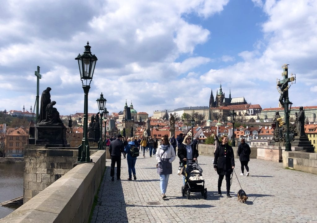 Three women, one pushing a stroller, walking along the stone Charles Bridge. You can see the steeples of the cathedral within Prague Castle poking out the background underneath a blue and white cloud-streaked sky.