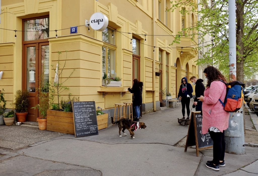 The outside of Etapa cafe, the building bright yellow, with a blackboard in front listing the specials in Czech. Four people and two dogs wait for their food outside the building.