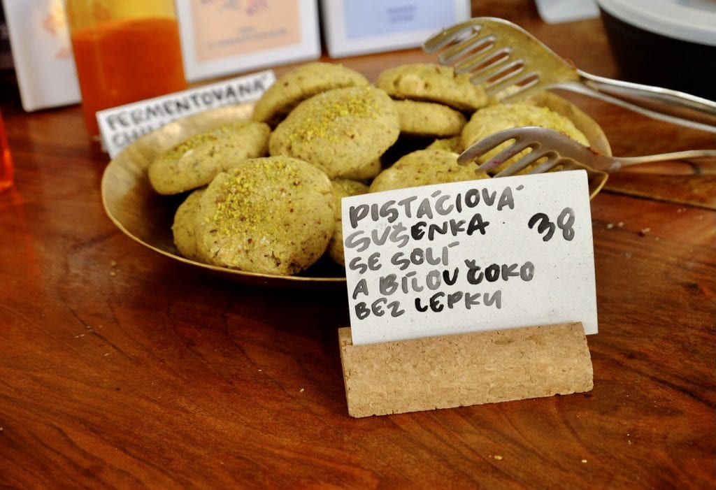 A big plate of cookies topped with pistachio dust, with a card in front describing the dish in Czech. Each cookie costs 38 crowns, about $1.81.