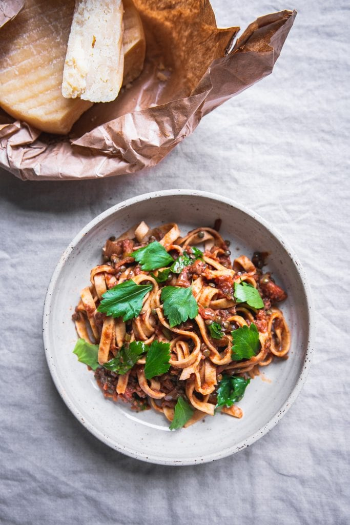 A plate of thick noodles served in what looks like a lentil sauce, topped with parsley leaves.
