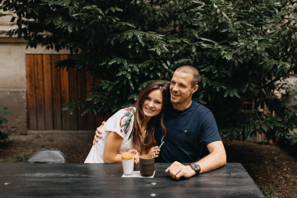 Gabi and Petr sitting at an outdoor wooden table. Gabi has long dark wavy hair and Petr has very short hair and has his arm around her. They are smiling. In front of them are two coffees.