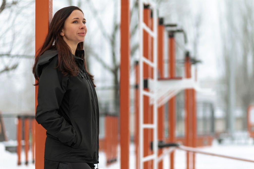 A woman standing in front of a wooden building, wearing a black gamma jacket and gazing ahead.