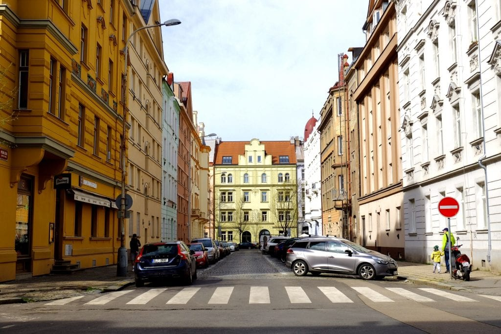 A city block in Prague: a pale yellow building in the background, crenellated with lots of angles, surrounded by a street with tan, white, and pale blue buildings, cars parked in front of each side.