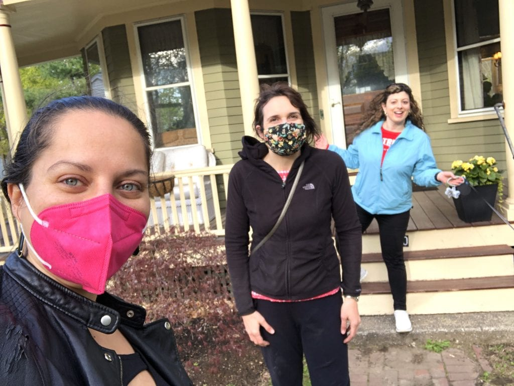 Kate and her two friends, Lisa and Alexa, standing apart from each other in front of a house. Kate wears a pink face mask, Lisa wears a flower patterned face mask, and Alexa wears no face mask but holds up her arms with a grin.