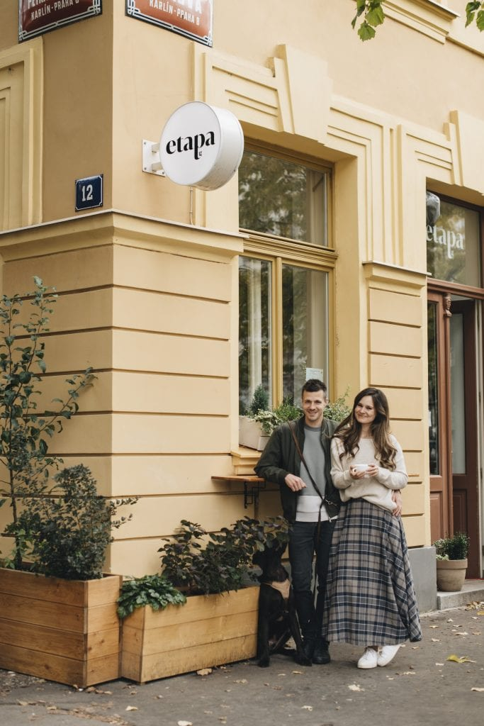 Peter and Gabi, a couple in their thirties, standing outside the cafe Etapa, which is a bright yellow building. Petr has short dark hair and wears a dark gray jacket and jeans, and Gabi has long dark wavy hair and wears a beige sweater and long gray plaid skirt.