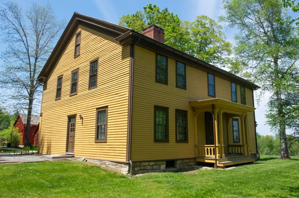A mustard yellow house with brown trim and a small porch in front, set among trees.