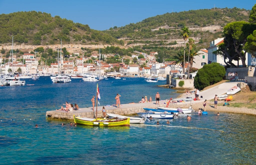 A pier jutting into the bright teal sea in Vis town, several people swimming in the water or sunning themselves. The town of Vis and several sailboats in the background.