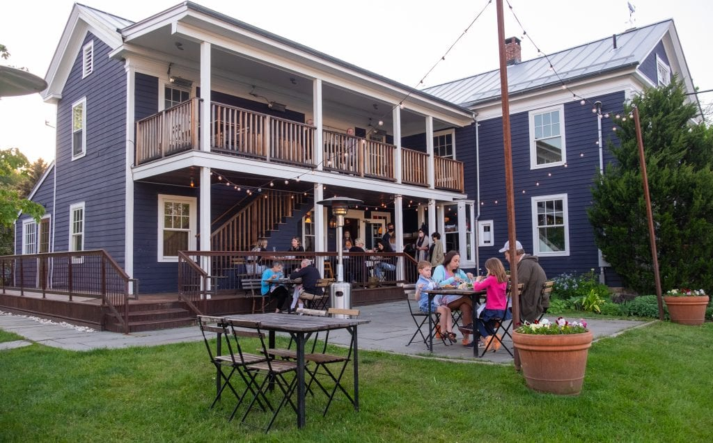 The Prairie Whale restaurant: a big navy blue house and many people eating outside on the porches and on the grass at distanced tables underneath Christmas lights.