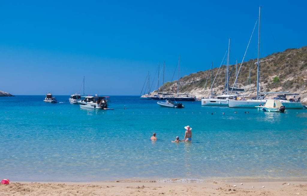 A sandy beach with calm, bright blue water. A man, woman and child playing in the water. Behind them, speedboats and sailboats.