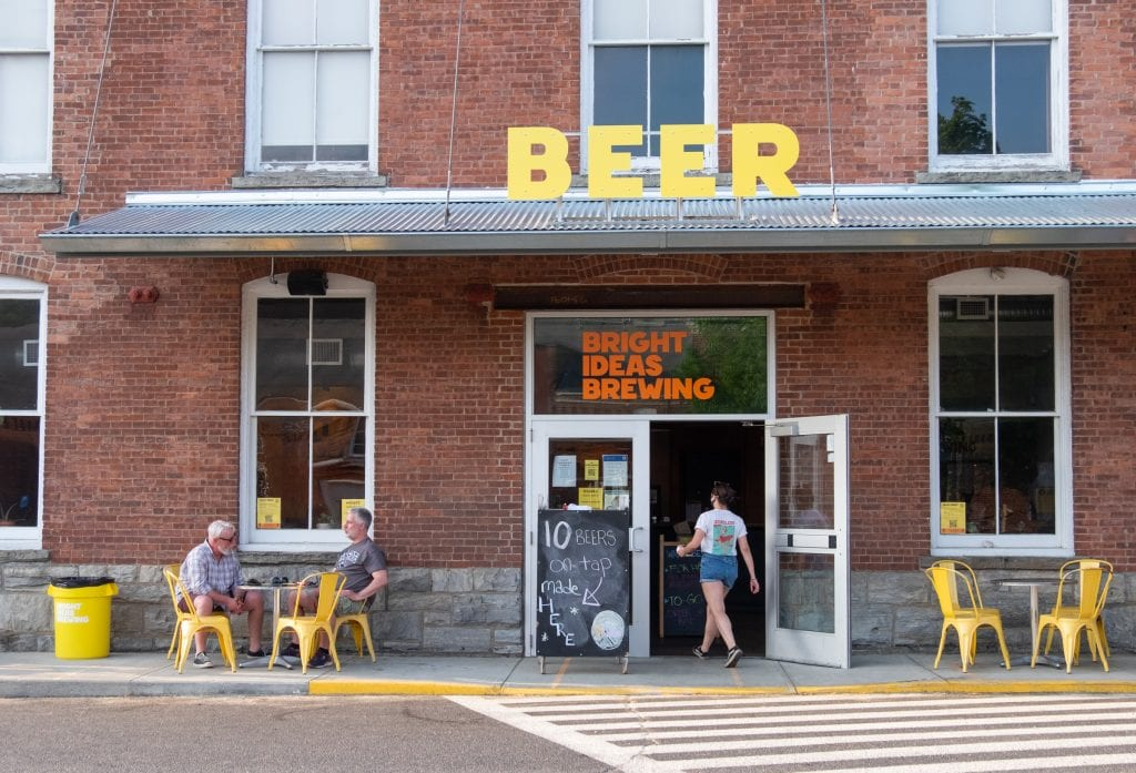 A brewery in a brick building. A big yellow sign reads BEER on top; you see two older man sitting at two bright yellow chairs outside, as a waitress walks into the front door.