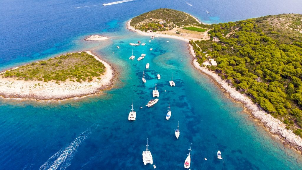 An aerial view of Budikovac, an island surrounded by bright blue water and dotted with several white boats.