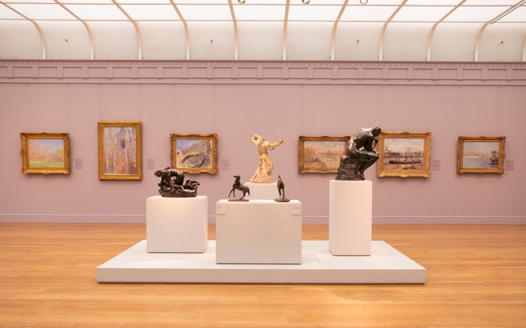 A pale lavender room at the Clark Institute with several gold-framed Impressionist paintings on the walls: in the foreground, several marble and metal sculptures. Two are of small horses; one is a man sitting and thinking with his head on his hand.