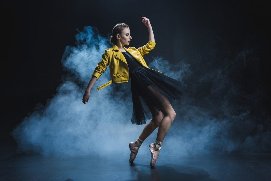 A ballerina in a black tutu, bright yellow leather jacket, and pink toe shoes, dancing on her toes as smoke is all around her.