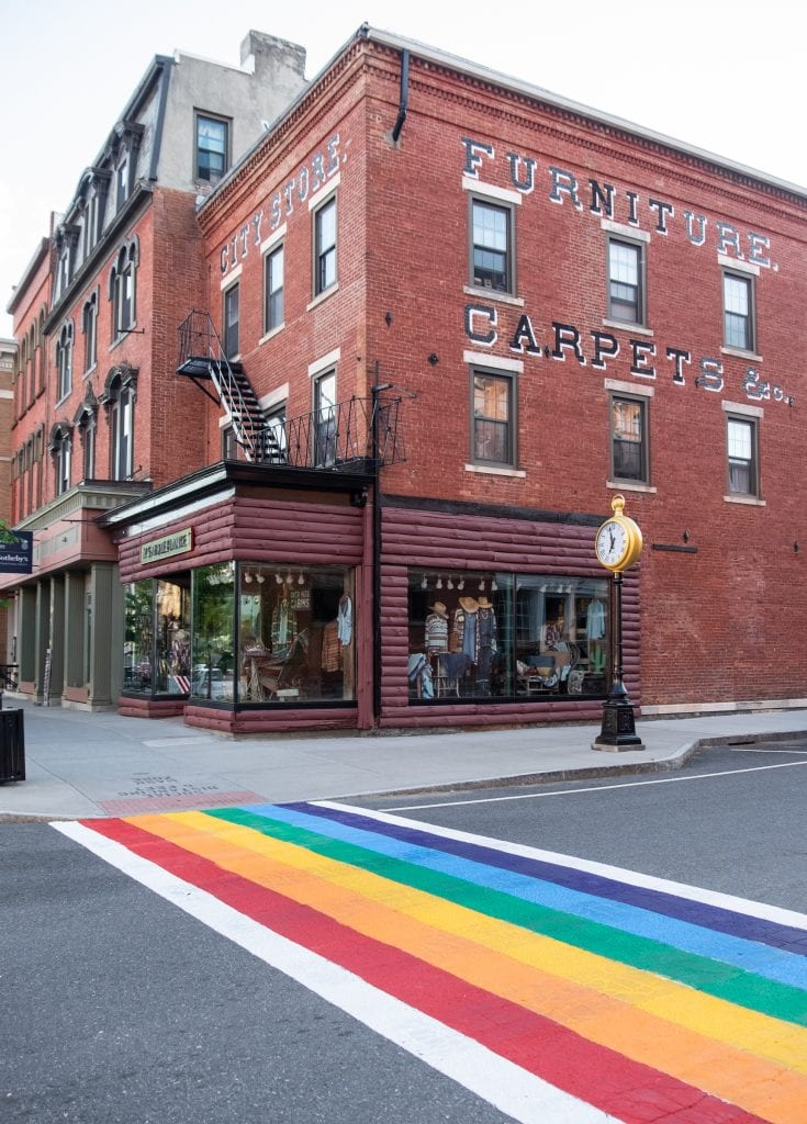 A large red brick building that used to be a furniture factory, with a boutique on the ground floor. In the foreground, a crosswalk painted rainbow colors.