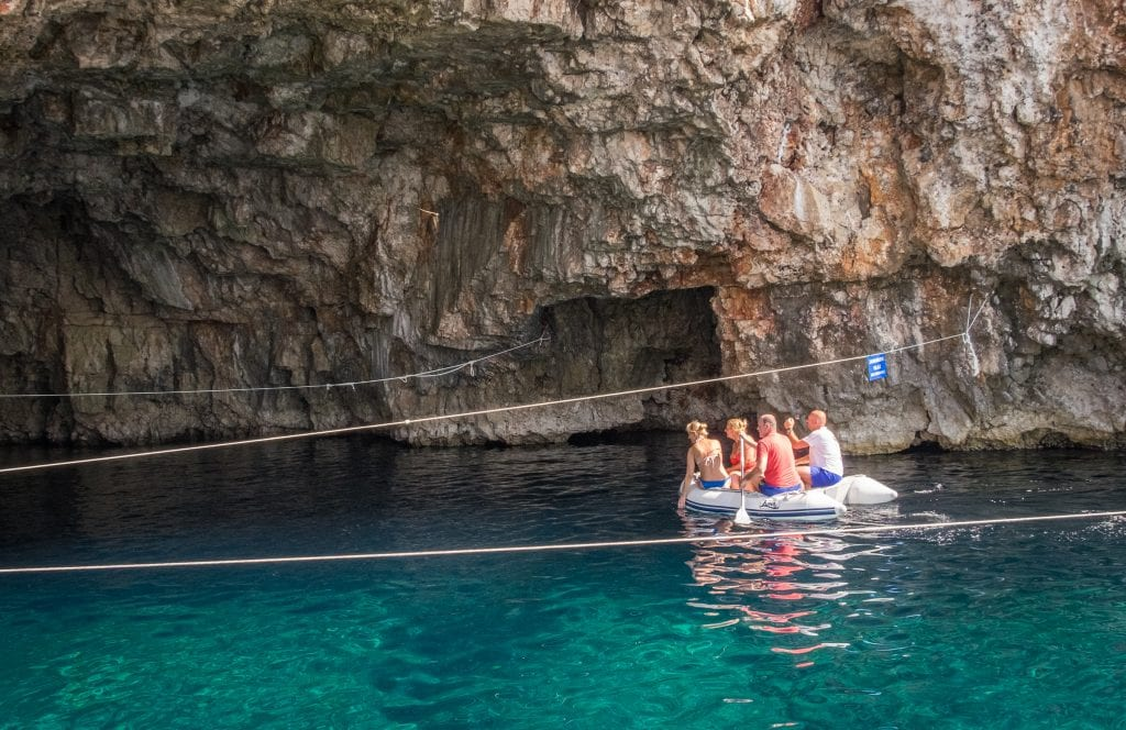 Four adults on a small inflatable boat, one paddling an oar. They are paddling into a rocky cave on top of greenish blue water.