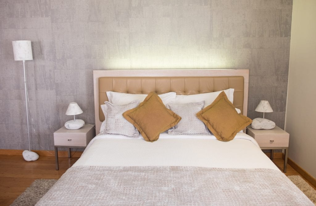 A bed with mustard and silver pillows. The side tables have lamps made of lumps of stone.