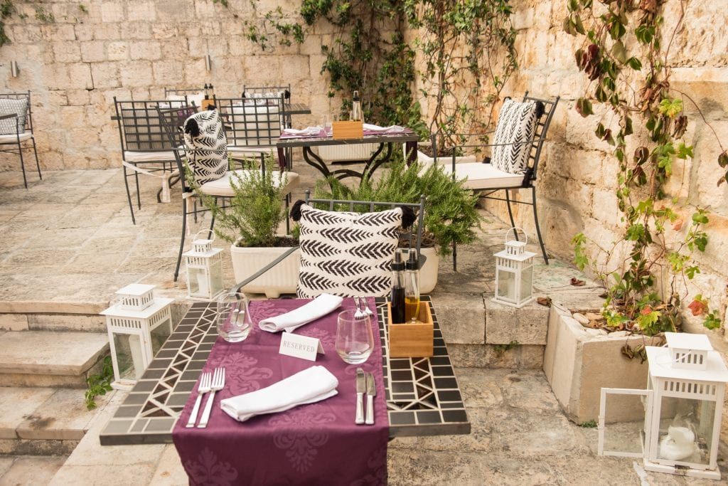 Another angle of the courtyard, tables covered with purple placemats, and plants and large white candle-filled lanterns on the ground.