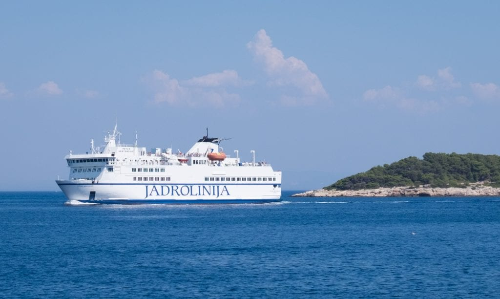 A large white ferry with JADROLINIJA on the side sailing past the edge of an island in Vis.