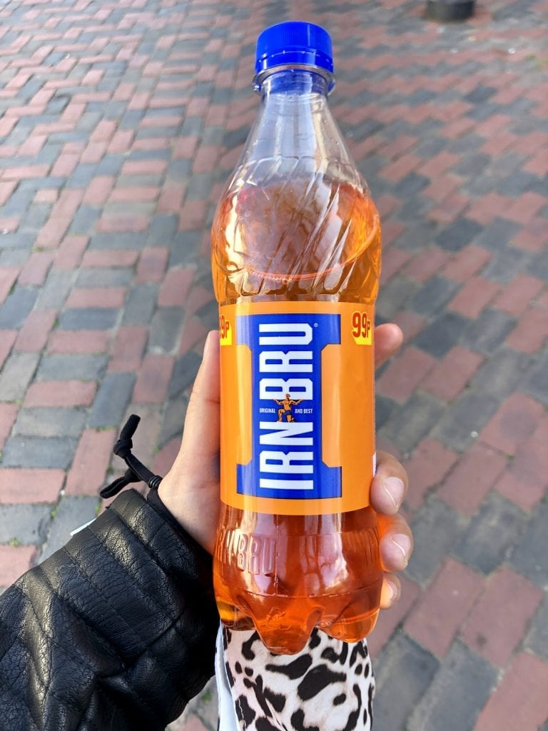 Kate holds a bottle of Iron Blu, a bright orange soda from Scotland.