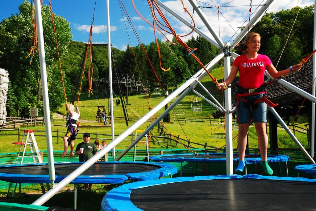 Two kids jumping on trampolines while wearing harnesses at Jiminy Peak Mountain Resort. In the background, empty ski lifts.
