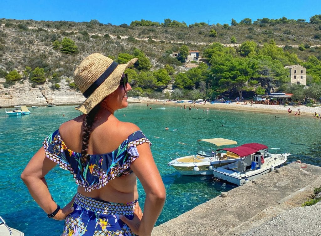 Kate standing in front of the bright blue-green water of the Adriatic. She faces away from the camera and wears a straw hat and sunglasses, a navy ruffled bikini top with tropical flowers on it, and harem pants that match the top.