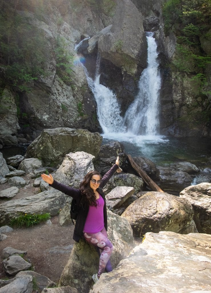 """Kate standing in front of Bish Bash Falls, a wild waterfall, and several rocks. Her hair is down and curly and she wears pink leggings with moons on them, a purple tank top, and a black zip-up hoodie on top. She has her arms pointed in the air as if to say """"I did it!"""""""