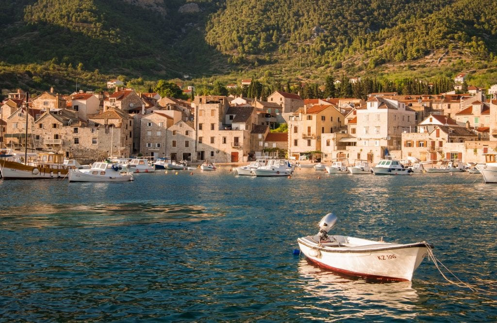 The harbor at Komiža, dozens of stone buildings in the golden afternoon light. A small white rowboat on the teal ocean in the foreground.