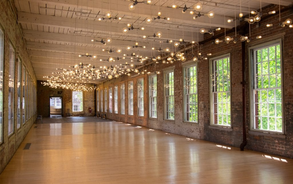 A long room at Mass MoCA -- it's long, red brick, covered with super huge windows letting in lots of light, and dozens of modern orb lights dangling from the white wooden ceiling.