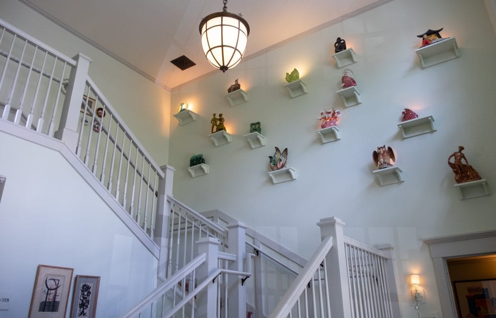 The hallway at the hotel: a white staircase and on a wall, several small shelves attached to the wall, each topped with a small glass sculpture.