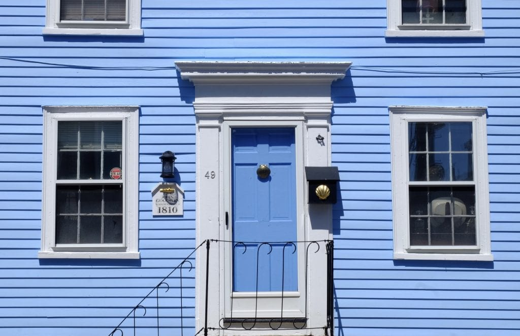 A periwinkle-blue house in Marblehead, Massachusetts, with a small plaque bearing 1810 John Goodman and a bright gold fish. On the mailbox is a bright gold seashell.