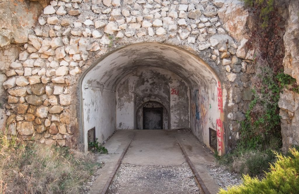 A military tunnel entrance, carved out of the mountain and covered with graffiti.