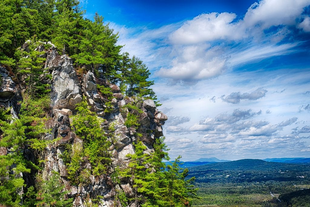 The edge of Monument Mountain, jagged and gray and topped with several evergreen trees, looking out over a cloudy sky and mountains in the distance.