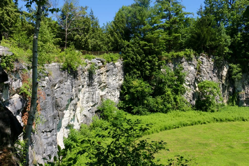 A tall gray rocky natural bridge in the middle of the state park.