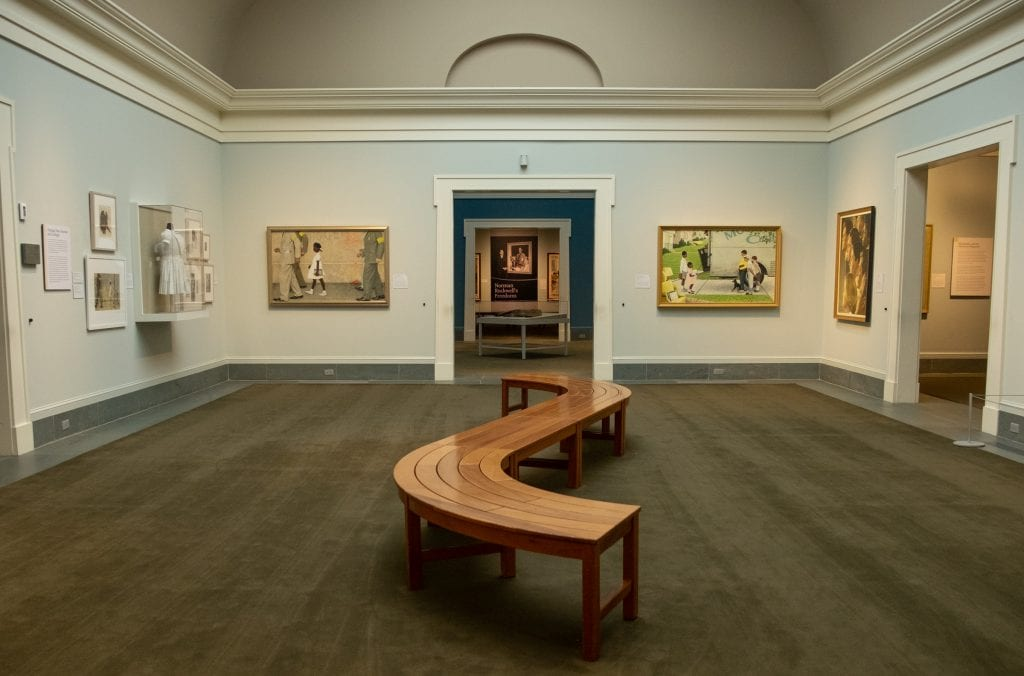 The Norman Rockwell Museum: a pale blue room with several paintings, including one of Ruby Bridges, the first young Black girl to integrate a segregated school in the South in the sixties.
