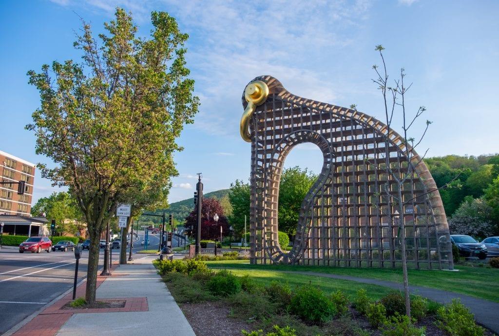 A modern sculpture that looks a bit like a bird built from an iron grid, a golden handle serving as beak and eyeball, overlooking a busy street in North Adams.