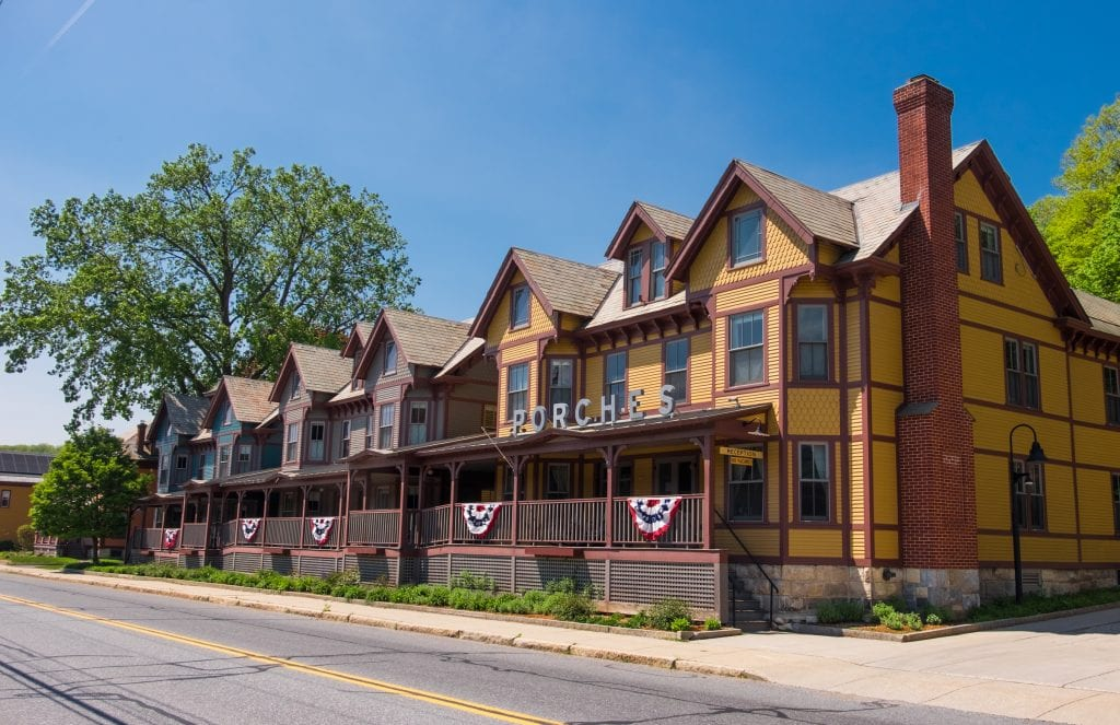 Porches: four Victorian homes joined together with a big wooden porch in front. One is blue, one is gray, and one is yellow, all with brown trim.