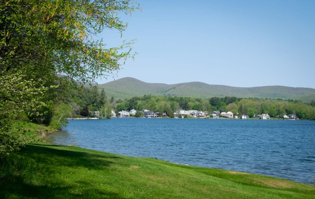 A bright blue lake with white houses on it in the distance, mountains behind them. It is grassy up to the lake's edge.