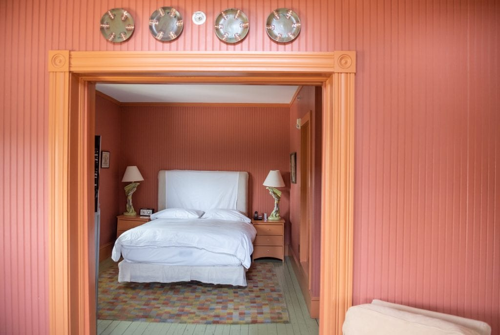 A room with textured stripe walls -- the walls are dark reddish orange and the trim is brighter orange, like the color of goldfish crackers. You see a white bed in the background in between two end tables with lamps that look like the sculpture of a man in green gauze.