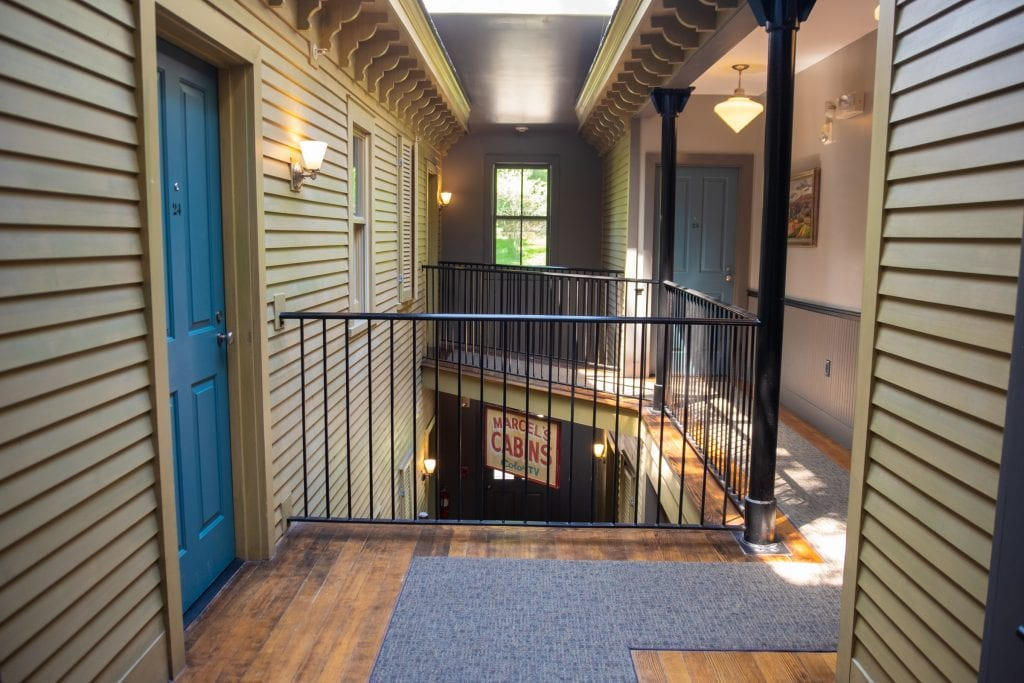 """In the hallway, you see several entrances to rooms. It's an open concept and you can see the floor below, which has a vintage sign reading """"Marcel's Cabins - Color TV."""""""