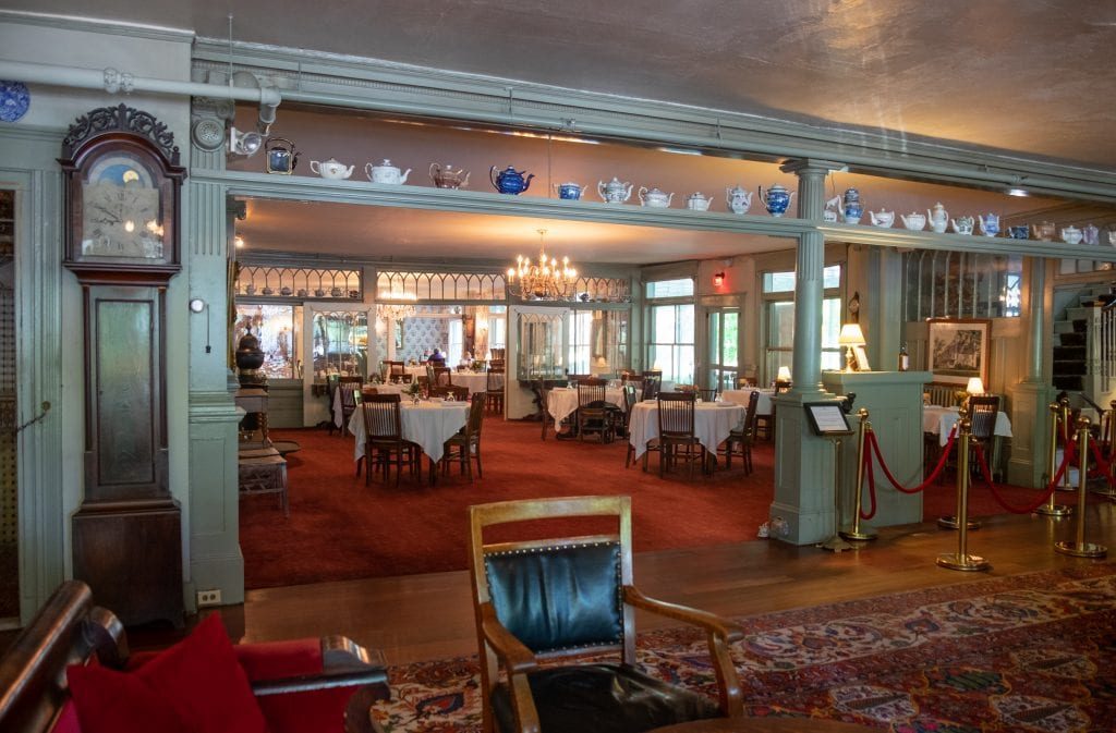 The entrance to the dining room at the Red Lion -- you see tables covered with white tableclothes, old-fashioned chandeliers, a dark wooden grandfather clock, and a shelf lined with all kinds of old-fashioned teapots for decoration.