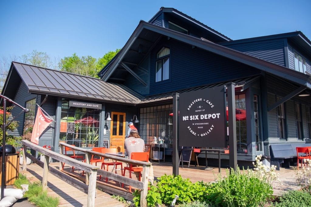 """A dark blue restored home with a big sign reading """"No Six Depot"""" in front' also, orange outdoor chairs and people sipping their coffee."""